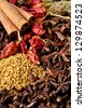 A close up of mixed whole spices including dried chilis, star anise,cloves,cinnamon and fenugreek - stock photo