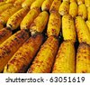 A close-up of rows of charred, delicious, grilled, yellow corncobs. - stock photo