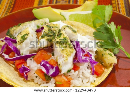 A close-up photo of a small fish taco plate with lime and avocado.