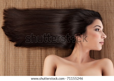 a close-up profile portrait of a young woman, laying on a spa mat. her hair is laying strait, in a horizontal direction.