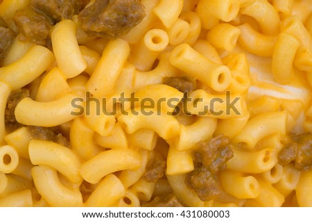 A close view of microwaved macaroni and cheese with hamburger chunks.