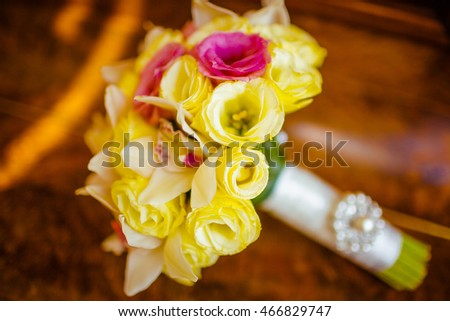 A closeup of tender wedding bouquet made of yellow and pink flowers