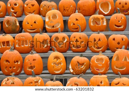 A collection of pumpkins with various different designs cut into them.