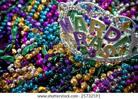 A colorful mardi gras crown or tiara lying on top of beads, holiday theme
