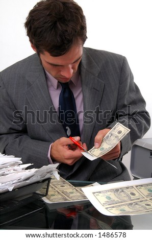 A counterfeiter cutting money