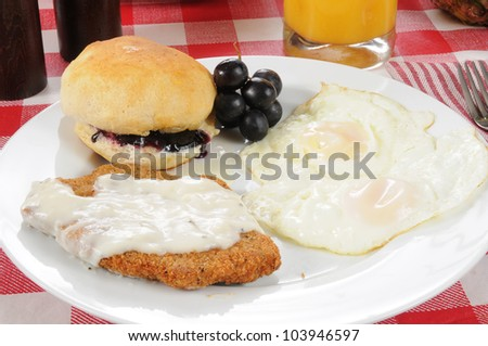 A country or chicken fried steak with fried eggs and a biscuit