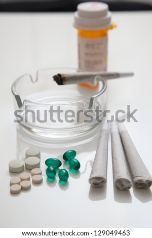 A couple of joints of medical marijuana with pills in the foreground and a prescription bottle in the background