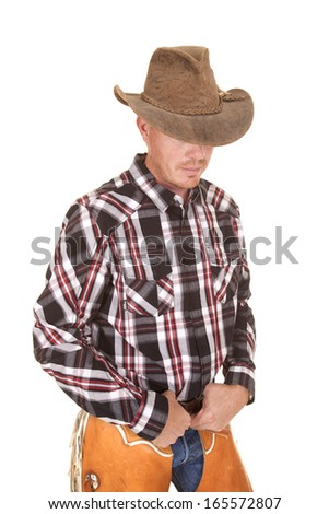A cowboy with his face hidden with his hands on his belt.