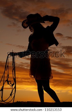 a cowgirl holding onto her bridle with a beautiful sunset in the background.