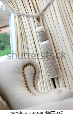 a cream coloured curtain tassel and curtain