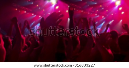 A crowd of spectators at a concert applauded their hands up. People in the red ramps. The blurred image for the background