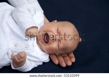 a crying 7 weeks old baby girl with her father´s hand holding her head over a blue blanket