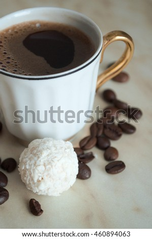 A cup of coffee , coffee beans and candy on the table