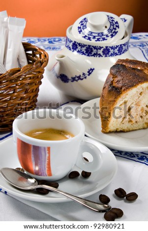 A cup of espresso coffee and a piece of cake for a perfect italian breakfast