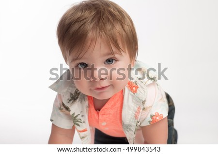 A curious ten month old, baby boy looking into the camera. He is crawling on a white, seamless background.