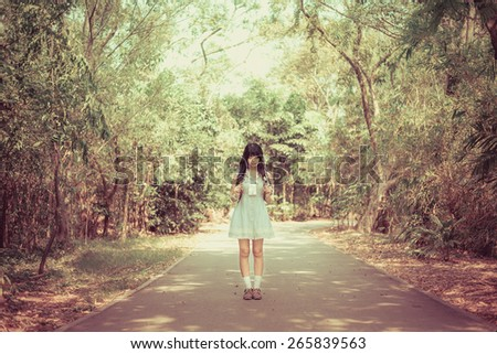 A cute Asian Thai girl is standing on a spring forest path alone in retro color