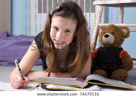 A cute girl does homework in her bedroom