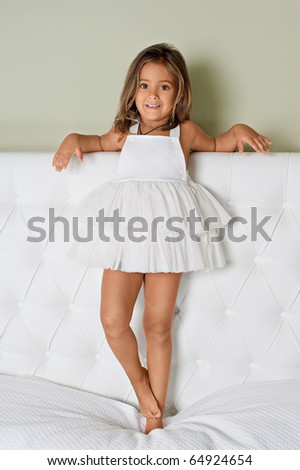 A cute young girl in white dress standing on bed