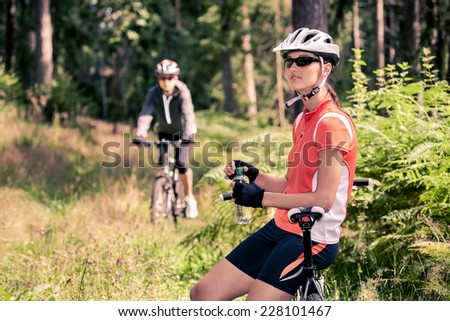 A cycling woman in front of the forest