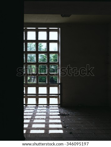 A dark room with window and sunlight
