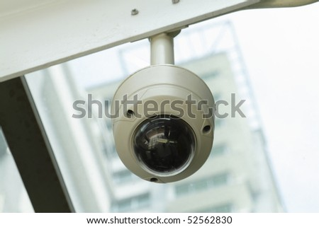 A dome-type security camera mounted on a ceiling