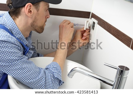 A Electrician changing a socket outlet in bathroom