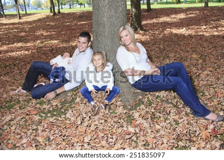 A Family enjoying golden leaves in autumn park