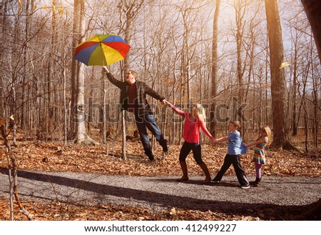 A family is holding hands together and flying up in a rainbow umbrella with sunlight outside for a imagination, support or happiness concept. Soft focus.