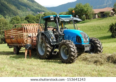 A farmer harvests the hay with the tractor