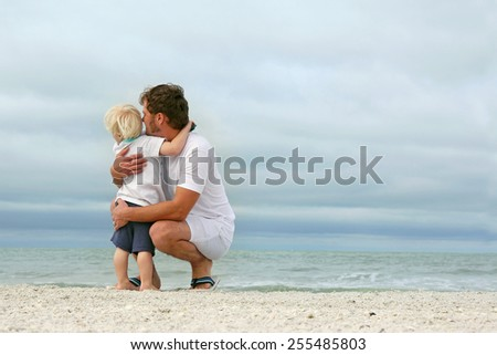 A father and his young toddler son are hugging as they stand on a white sand beach and look out over the ocean while on vacation.