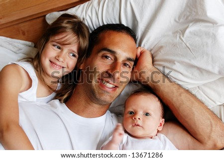 A father relaxing in bed with his two children