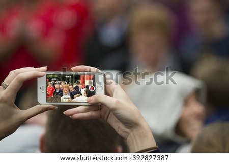 A female hand takes a cellphone video of Prince Harry of Wales who is meeting members of the public at the University of Canterbury on May 12, 2015 in Christchurch, New Zealand.