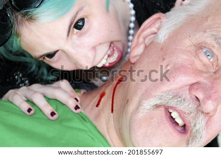 A Female Vampire with Blue Hair and Black Eyes Bites an unsuspecting victim and drinks his blood for her dinner. On white with room for your text
