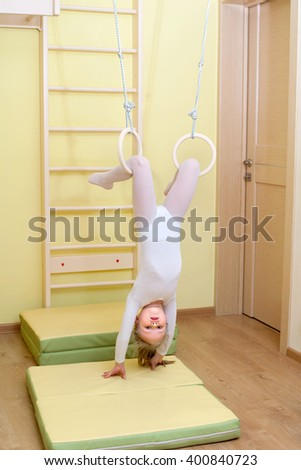 A five years girl is making exercises at flying rings at home
