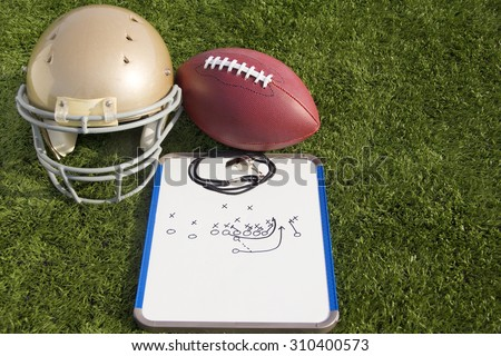A football helmet, ball and clipboard with a play drawn on it.