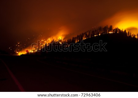 A forest fire burns at night alongside an interstate highway in western Montana.  Seen