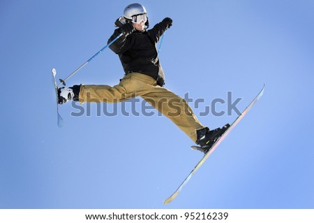 a freestyle skier in the middle of a trick legs and arms spread