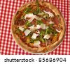 A fresh pizza under red and white tablecloth background - stock photo