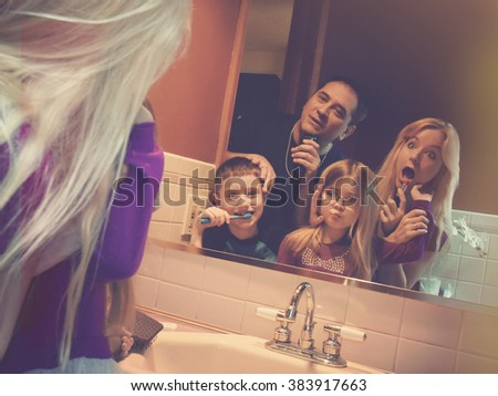 A funny family is getting ready in the morning and rushing in the bathroom in a tight space for a routine, schedule or lifestyle concept.