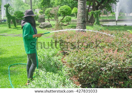 A gardener with a hat and ,ask is watering trees.