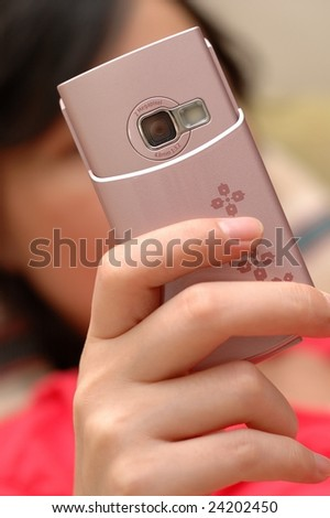 A girl is using mobile phone taking a photo.