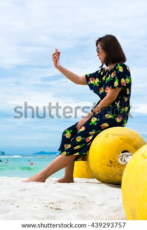 A Girl sitting on Buoyancy near sea, take a photo with herself