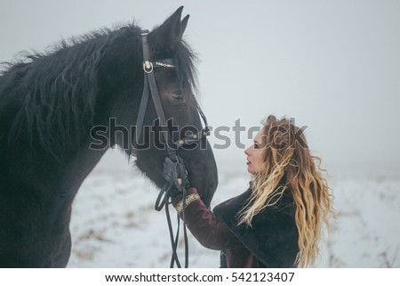 a girl with a horse in a field in winter.