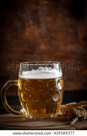 A glass of fresh cold light beer with gourmet hamburgers and wheat in a bar and a dark pub