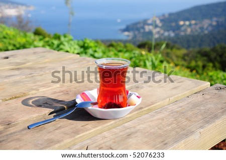 a glass of tea on a wooden table on nature
