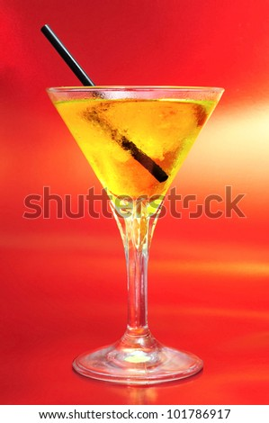a glass with a yellow cocktail on a red background