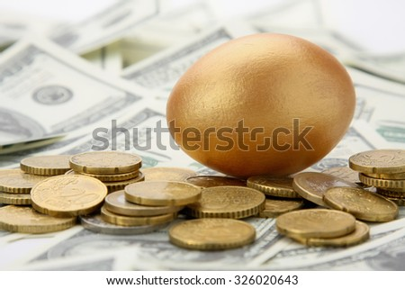A gold egg lying on dollars and coins.