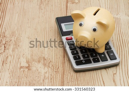 A golden piggy bank and calculator on a wood background with copy space for your message