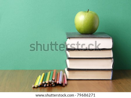 A green apple on a pile of books and pencils on the desk