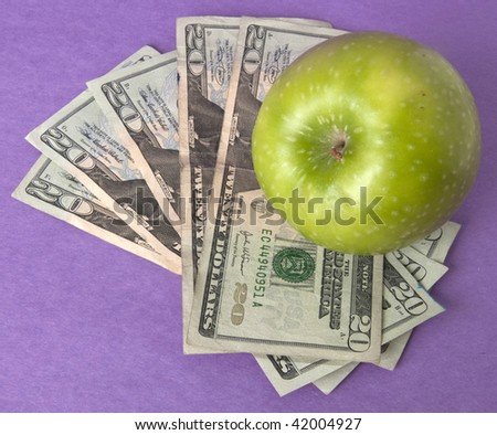 A green apple sits on top of a pile of $20 bills to illustrate the cost of education, food, or health care.